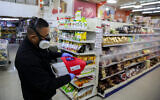 Workers disinfect the Bar Kol Supermarket in Safed, March 16, 2020, as part of measures to prevent the spread of the coronavirus. (David Cohen/Flash90)