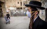 An ultra-Orthodox youth plays with a face mask in the neighborhood of Mea Sharim, Jerusalem, on March 16, 2020 (Yonatan Sindel/Flash90)