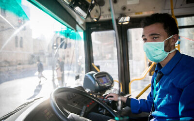 A bus driver sits in a bus and wears a face mask for fear of the coronavirus in downtown Jerusalem, March 16, 2020. (Yonatan Sindel/Flash90)