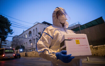 A Magen David Adom worker arrives to test a patient with symptoms of COVID-19, in Jerusalem on March 16, 2020. (Yonatan Sindel/Flash90)