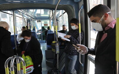 Israelis wearing face mask for fear of the coronavirus are seen in public transport in Jerusalem on March 17, 2020. (Yossi Zamir/Flash90)