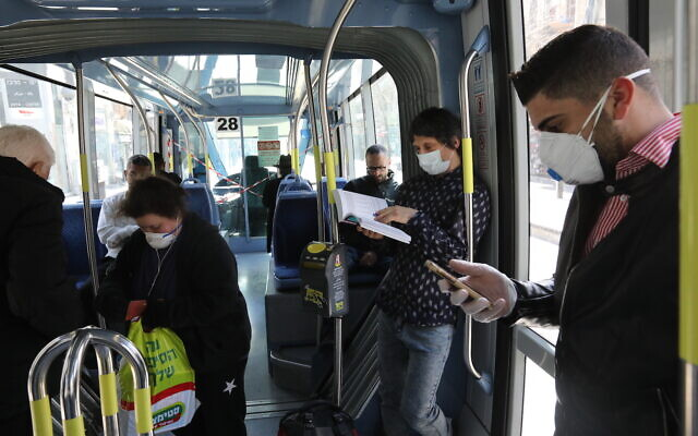 Israelis wearing face mask for fear of the coronavirus are seen in public transport in Jerusalem on March 17, 2020. (Yossi Zamir/Flash90)