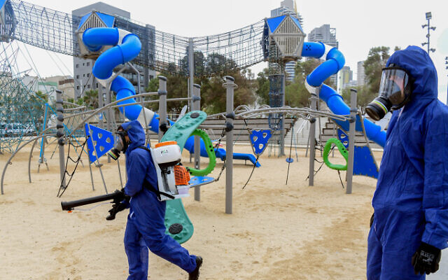 Workers wearing protective clothes disinfect a public playground in the coastal city of Bat Yam, on March 18, 2020 (Flash90)