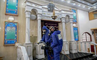 Workers wearing protective clothes disinfect a synagogue in Bat Yam, on March 18, 2020, as part of measures to prevent the spread of the Coronavirus. (Flash90)