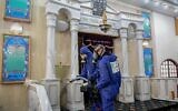 Workers wearing protective gear against the coronavirus disinfect a synagogue in Israel, March 18, 2020. (Flash90)