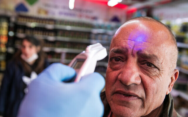 A security guard check the temperature of a customer to identify if he has a fever in a  Rami Levy supermarket in Jerusalem on  March 18, 2020. (Olivier Fitoussi/FLASH90)