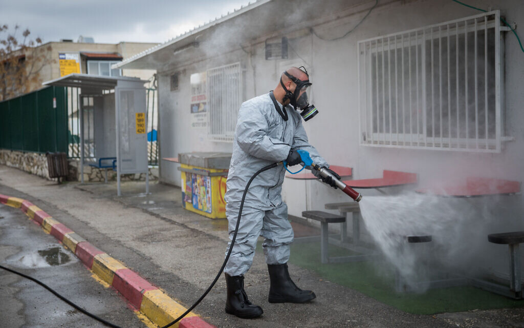 An Israeli firefighter wearing protective clothes disinfects a bus station in the ultra-Orthodox town of Kiryat Ye'arim (Telz-Stone), on March 18, 2020, after seventeen of the city's residents were found to have coronavirus. (Yonatan Sindel/Flash90