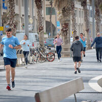 People run near the beach in Tel Aviv on March 19, 2020 (Avshalom Sassoni/Flash90)
