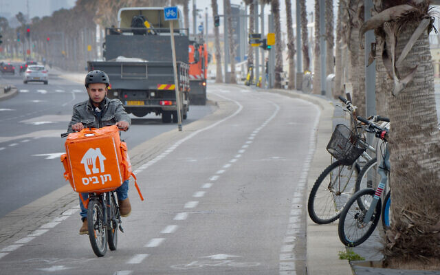 A delivery man rides his bicycle near the beach in Tel Aviv on March 19, 2020. (Avshalom Sassoni/Flash90)
