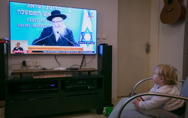 An Israeli child watch as Health Minister Yaakov Litzman holds a live press conference on the new government restrictions for the public regarding the coronavirus on March 19, 2020. (Chen Leopold/Flash90)