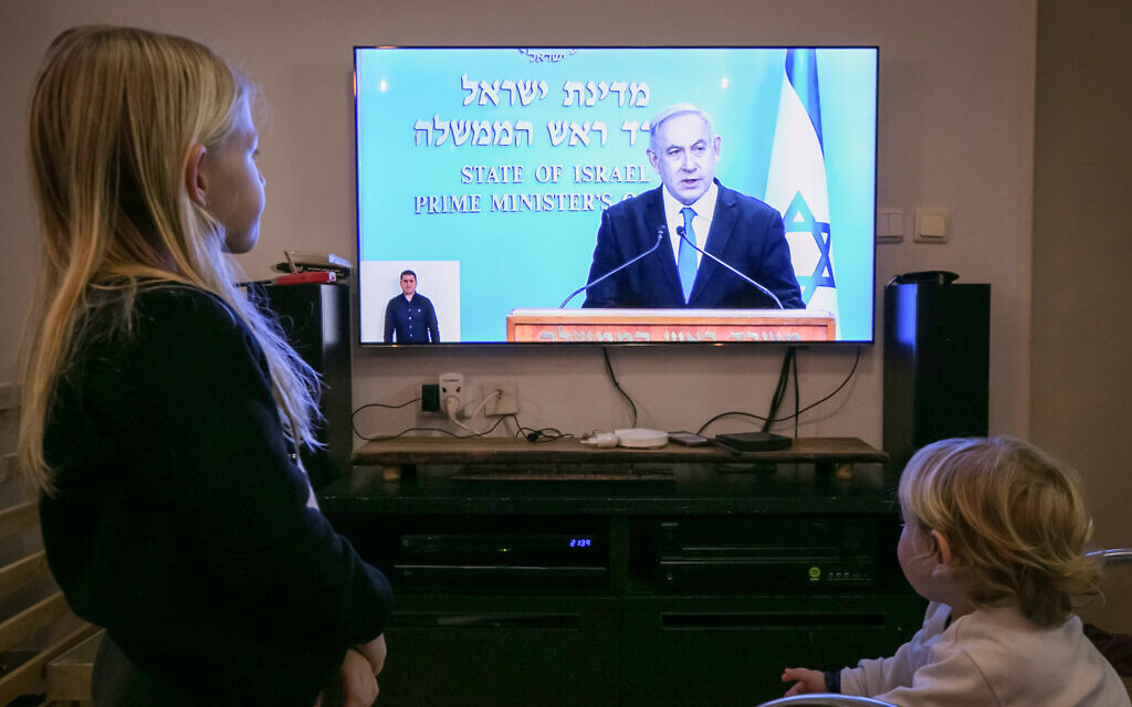 Israeli children watch as Israeli prime minister Benjamin Netanyahu holds a live press conference on the new government restrictions for the public regarding the coronavirus COVID-19 on March 19, 2020. (Chen Leopold/Flash90)