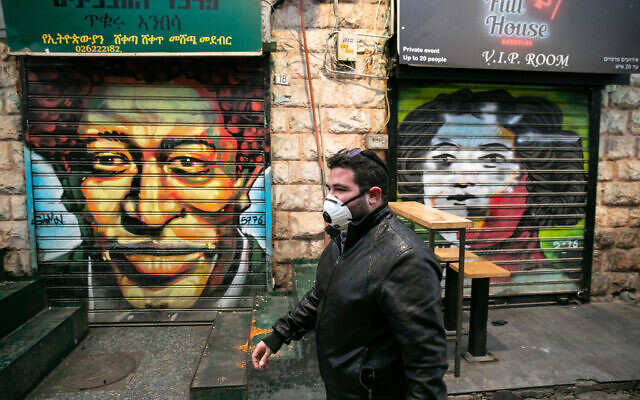 An Israeli man wearing a face mask for fear of the coronavirus walks in the Mahane Yehuda Market Jerusalem on March 20, 2020.(Olivier Fitoussi/Flash90)