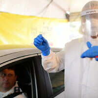 Magen David Adom staff wear protective clothing at a drive-through site to collect samples for coronavirus testing in Tel Aviv, March 20, 2020. (Tomer Neuberg/Flash90)