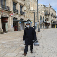 A man wearing a face mask for fear of the coronavirus walks near by the Jaffa Gate in the Old City of Jerusalem on March 21, 2020. (Yossi Zamir/Flash90)