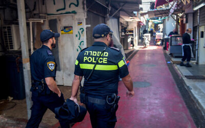 Israeli police officers close shops following the government decision, at the Carmel market in Tel Aviv on March 22, 2020. (Avshalom Sassoni/Flash90)