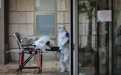 Illustrative: Magen David Adom workers transferring a woman at Hadassah Ein Karem hospital, in Jerusalem, on March 22, 2020. (Flash90)