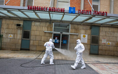 Israeli firefighter wearing protective clothes disinfects the entrance of the emergency of Hadassah Ein Karem hospital in Jerusalem on March 22, 2020. (Olivier Fitoussi/Flash90)
