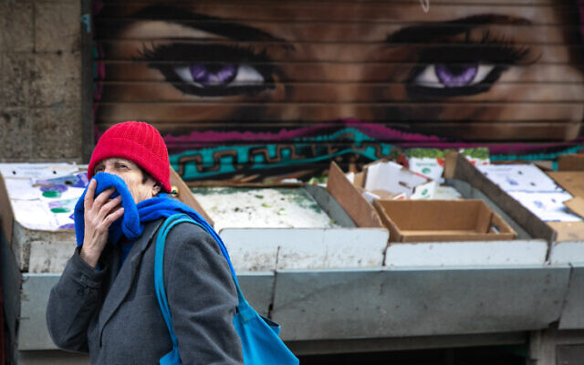 An Israeli woman, covering her nose and mouth for fear of the coronavirus, at the Mahane Yehuda Market in Jerusalem on March 22, 2020. (Olivier Fitoussi/Flash90)