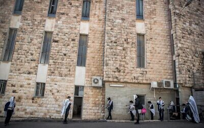 Men pray outside a synagogue in Bayit Vegan, Jerusalem, on March 22, 2020 (Yonatan Sindel/Flash 90)
