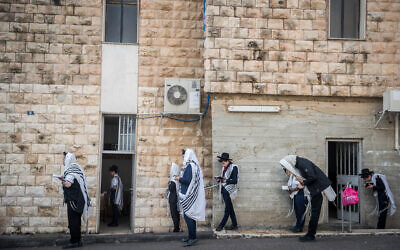 Jewish men pray outside a synagogue while maintaining social distancing as part of the campaign against the coronavirus outbreak, in Bayit Vegan, Jerusalem, on March 22, 2020. (Yonatan Sindel/Flash90)