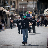A photojournalist wears face mask and gloves for fear of the coronavirus at the Mahane Yehuda Market in Jerusalem on March 22, 2020. (Yonatan Sindel/Flash90)