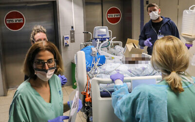 Illustrative: Staff and Ichilov hospital in Tel Aviv move a patient to a new ward, March 22, 2020. (Yossi Zamir/Flash90)