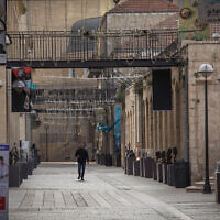 An Israeli man walks past closed stores in the empty Mamila Mall in Jerusalem on March 23, 2020. (Nati Shohat/Flash90)