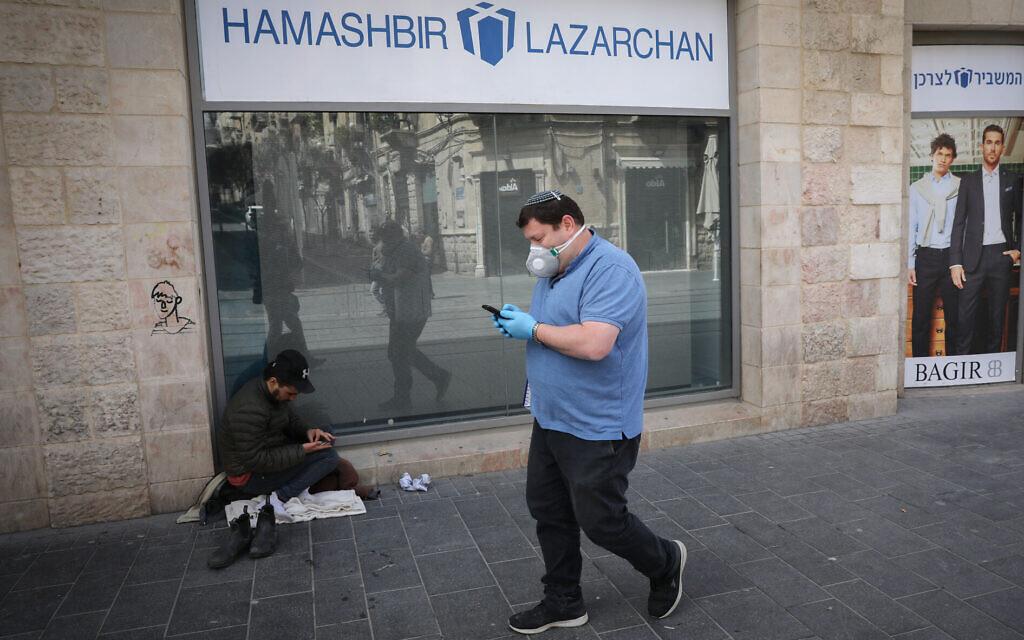 Um homem usando uma máscara facial por medo do coronavírus, passa por um sem-teto perto de um shopping fechado em Jerusalém em 23 de março de 2020. (Olivier Fitoussi / Flash90)
