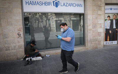 A man wearing a face mask for fear of the coronavirus, walks past a homeless person near a closed shopping mall  in Jerusalem on March 23, 2020. (Olivier Fitoussi/Flash90)