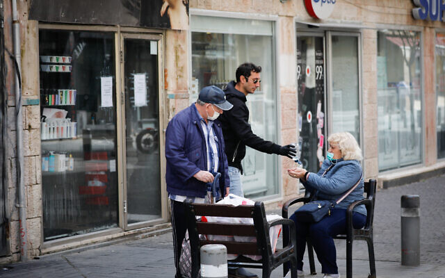 A man offers elderly Israelis hand sanitizer to desinfect their hands for fear of coronavirus, in Jerusalem on March 22, 2020. (Olivier Fitoussi/FLASH90)