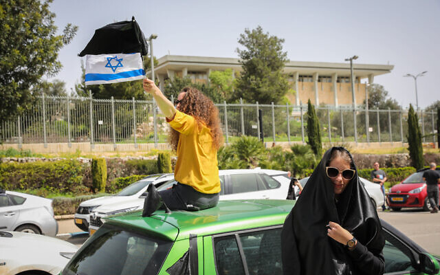 Protesters take part in a demonstration against government actions explained as precautions due to the coronavirus outbreak but which they see as anti-democratic, seen here outside the Knesset in Jerusalem, March 23, 2020. (Olivier Fitoussi/Flash90)