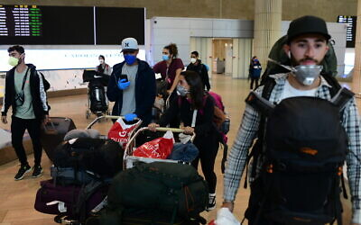 Illustrative: Israeli travelers who had been stranded in South America arrive at Ben-Gurion airport on March 23, 2020, from Sao Paolo, Brazil, through New York. (Tomer Neuberg/Flash90)