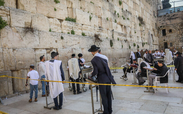 Jewish men pray at the Western Wall, in the Old City of Jerusalem while adhering to government-ordered social-distancing measures due to the coronavirus outbreak, March 23, 2020. (Yossi Zamir/Flash90)