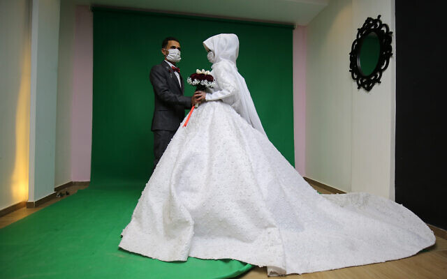 Palestinian groom Mohamed abu Daga and his bride Israa wear face masks amid the novel coronavirus epidemic, during a photoshoot at a studio before their wedding ceremony in Khan Yunis in the southern Gaza Strip, on March 23, 2020. (Abed Rahim Khatib/ Flash90)