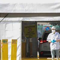 A Magen David Adom worker is seen at a drive-through coronavirus testing facility in Jerusalem on March 24, 2020. (Olivier Fitoussi/Flash90)
