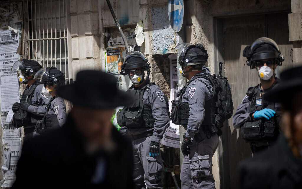 Israeli police officers seen raiding the ultra-Orthodox Jewish neighborhood of Mea Shearim in Jerusalem, closing shops and dispersing public gatherings in an effort to contain the spread of the coronavirus, March 24, 2020. (Yonatan Sindel/Flash90)