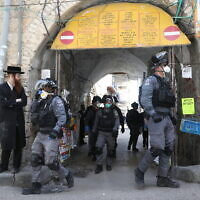 Police officers in the ultra-Orthodox Jewish neighborhood of Mea Shearim in Jerusalem close shops and disperse public gatherings following government orders in an effort to contain the spread of the coronavirus. March 24, 2020. (Yonatan Sindel/Flash90)