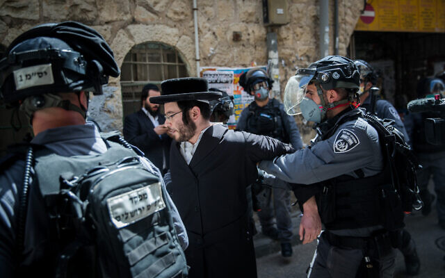 Police officers seen during a raid on the ultra orthodox Jewish neighborhood of Mea Shearim, as they close shops and disperse public gatherings following the government decisions in an effort to contain the spread of the coronavirus. March 24, 2020. (Yonatan Sindel/Flash90)