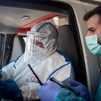 Magen David Adom ambulance workers wearing protective clothing as a preventive measure against the coronavirus bring a woman suspected having the coronavirus to the Shaare Zedek Medical Center in Jerusalem, March 24, 2020. (Yonatan Sindel/Flash90)