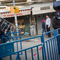 Jerusalem Municipality workers close the entrances to the Mahane Yehuda market in Jerusalem on March 24, 2020 (Yonatan Sindel/Flash90)