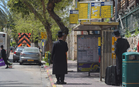Ultra Orthodox Jewish men wait for a bus in Bnei Brak on March 25, 2020 (Avshalom Sassoni/Flash90)