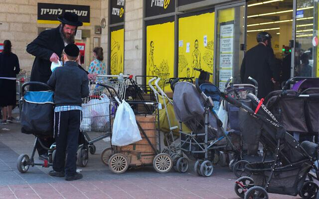 Ultra Orthodox Jews outside a supermarket in Bnei Brak on March 25, 2020 (Avshalom Sassoni/Flash90)