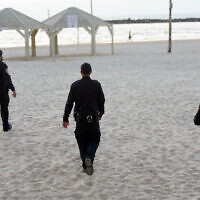 Police patrol on the Tel Aviv beach boardwalk on March 25, 2020. (Avshalom Sassoni/Flash90)