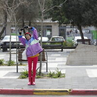 A woman does morning exercises in the nearly empty Beit Hakerem neighborhood in Jerusalem on March 25, 2020 (Olivier Fitoussi/Flash90)