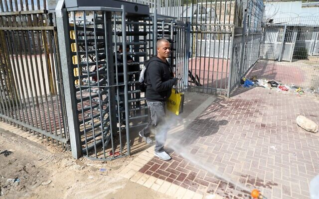Palestinian health workers disinfect Palestinian laborers as they cross back from Israel at a checkpoint in Tarqumiya on March 25, 2020 (Wisam Hashlamoun/Flash90)