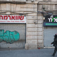 A man passes shuttered stores on Jaffa Street in Jerusalem on March 25, 2020 (Yonatan Sindel/Flash90)