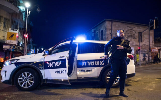 Israeli police officers stand guard in the Geula neighborhood in Jerusalem on March 25, 2020, as they arrive to close shops in the area following a state order. (Yonatan Sindel/Flash90)