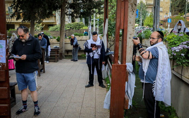 Jewish men pray outside a synagogue at the Nachlaot neighborhood in Jerusalem on March 25, 2020 (Yossi Zamir/Flash90)
