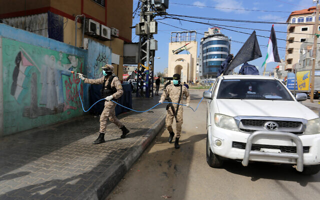 Members of the Palestinian Islamic Jihad terror group's armed wing, the Al-Quds Brigades, spray disinfectant in the streets of Rafah in the southern Gaza Strip, during a campaign aimed at slowing down the spread of the novel coronavirus, March 26, 2020. (Abed Rahim Khatib/Flash90)