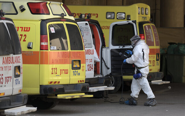 Medical personnel cleanse and disinfectian ambulance at Tel Aviv's Dan Panorama hotel which has been turned into coronavirus quarantine facility, March 26, 2020. (Gili Yaari /Flash90)